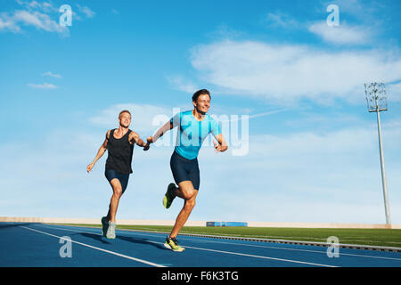 Shot of professional male athletes passing over the baton while running on the track. Athletes practicing relay - Stock Photo