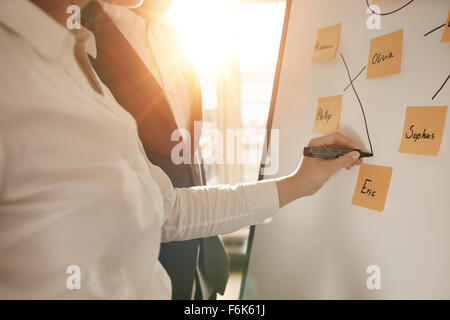 Cropped shot of business people making pairs of employees for making efficient sales team. Woman pairing sticky - Stock Photo