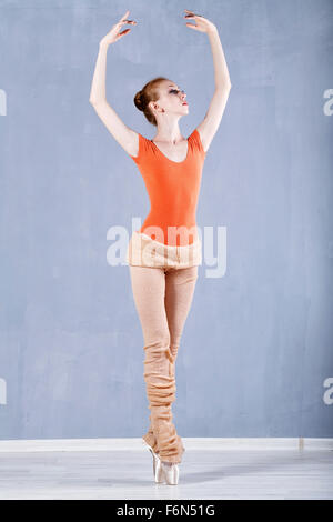 Classical ballet in the performance a slim ballerina. Girl rehearses dance. Girl stands on tiptoe and raised her - Stock Photo