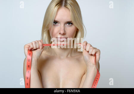Close up Shirtless Young Woman holding a Measuring Tape and Looking at the Camera Against Gray Wall Background. - Stock Photo
