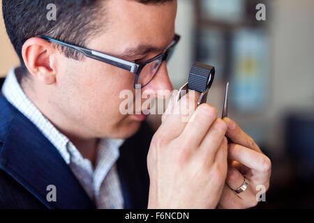Jeweler examining diamond thoroughly through loupe - Stock Photo