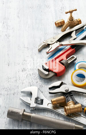 various type of plumbing tools on white textured background - Stock Photo