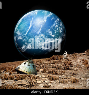 An astronaut surveys his situation after being marooned on a barren and rocky moon. An alien, and water covered - Stock Photo