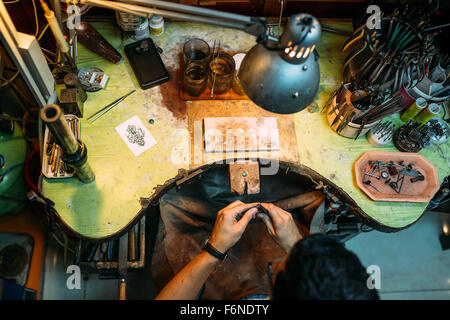 Goldsmith working on his bench, crafting jewelry - Stock Photo