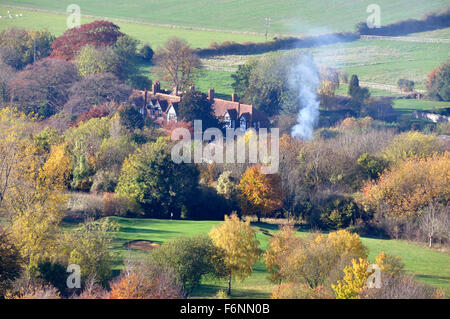 Bucks - Chiltern Hills - on Coombe Hill - view over autumn in the trees - cottages rooftops - drifting smoke from - Stock Photo