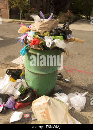 Overflowing garbage can in Brooklyn, NY. - Stock Photo