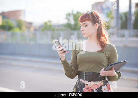 Half length of young handsome caucasian redhead woman using a smartphone, looking downward and tapping the screen - Stock Photo