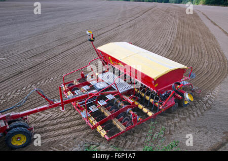Tractor sowing crop wheat seeds in freshly plowed farm field - Stock Photo