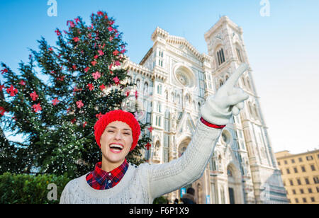Hey, take a look! Happy young travel lover in white sweater pointing on something in front of traditional christmas - Stock Photo