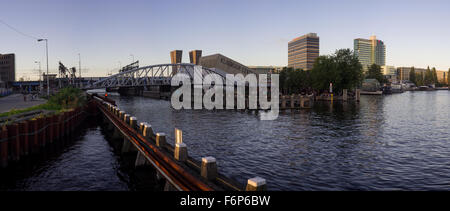 Panoramic view on the modern Oosterdok Swing Bridge across the Oosterdok Canal at the sunset in Amsterdam (The Netherlands) - Stock Photo