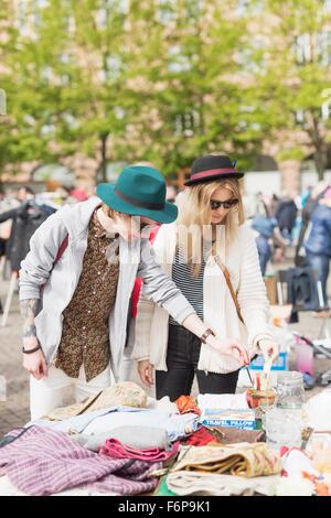 Young man and woman wearing sunglasses shopping at flea market - Stock Photo