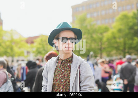 Thoughtful young man wearing sunglasses standing at flea market - Stock Photo