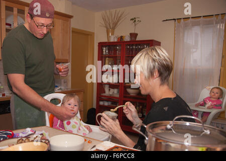 Mom and dad feeding two young twin daughters in their kitchen. Minneapolis Minnesota MN USA - Stock Photo