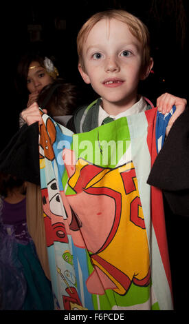 Costumed trick or treater holds up his Halloween candy bag. St Paul Minnesota MN USA - Stock Photo