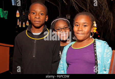 Three African American kids trick or treating Halloween night. St Paul Minnesota MN USA - Stock Photo