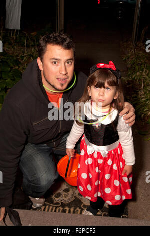 Dad bringing his reluctant costumed daughter out for Halloween trick or treats. St Paul Minnesota MN USA - Stock Photo