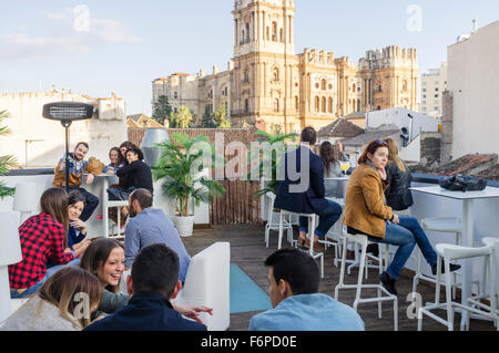 People at outdoors rooftop bar of Chinitas Urban Hostel with Cathedral in background. Malaga, Andalusia, Spain - Stock Photo