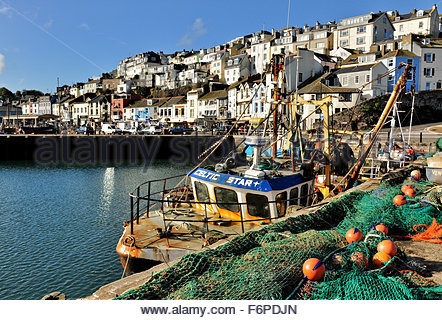 A fishing boat with fishing nets on the Quayside in Brixham Harbour, Devon - Stock Photo
