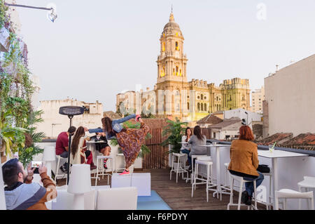People at rooftop terrace bar with illuminated Cathedral in background. Malaga, Andalusia, Spain - Stock Photo