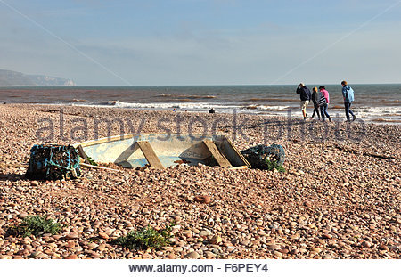 People walking along the beach at Sidmouth in Devon. - Stock Photo