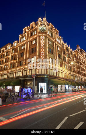 The famous Harrods department store illuminated at night with car passing lights in London - Stock Photo