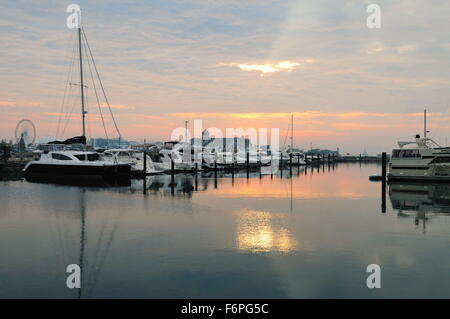 Not long after sunrise the sun attempts to break through cloud cover above pleasure craft in Chicago's DuSable Harbor. - Stock Photo
