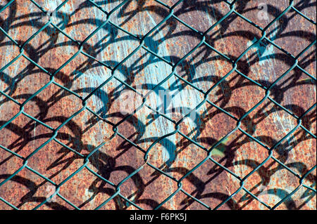 Graphic patterns created by wire mesh, hurricane, or cyclone steel fence - Stock Photo