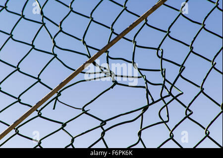 Torn hole in a wire mesh, hurricane, or cyclone steel fence - Stock Photo