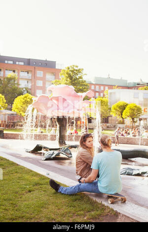 Couple sitting on skateboard at park with fountain in background - Stock Photo