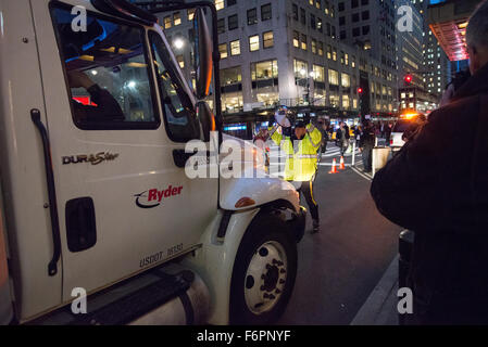 New York, United States. 18th Nov, 2015. A police officer (center) directs a truck to pull into place for inspection - Stock Photo