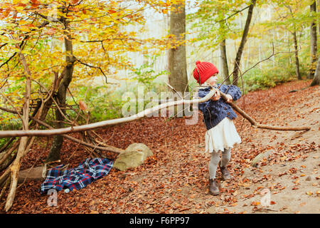 Girl carrying tree in forest - Stock Photo