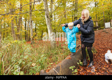 Mother assisting son walking on log - Stock Photo