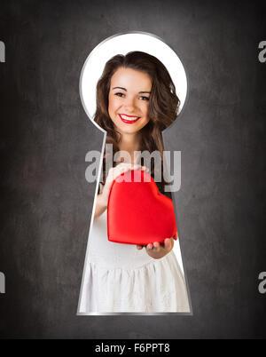 Someone peeking through the keyhole of the happy girl - Stock Photo