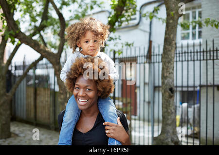 Mother carrying daughter on shoulders outdoors - Stock Photo