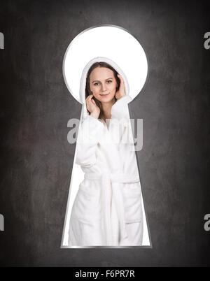 Someone peeking through the keyhole of the woman - Stock Photo