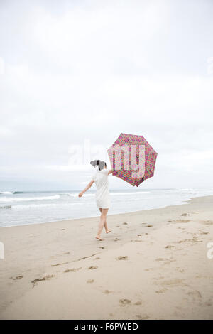 Woman walking in wind with umbrella on beach - Stock Photo