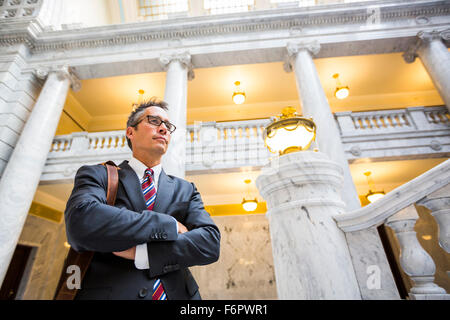Mixed race businessman standing in courthouse - Stock Photo