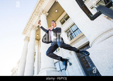 Mixed race businessman jumping for joy outside courthouse - Stock Photo