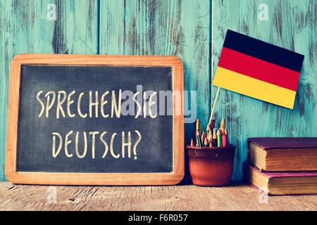 a chalkboard with the question sprechen sie deutsch? do you speak german? written in german, a pot with pencils, - Stock Photo