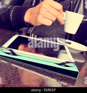 closeup of a young man taking a cup of coffee with a tablet computer on the table, in the terrace of a cafe - Stock Photo