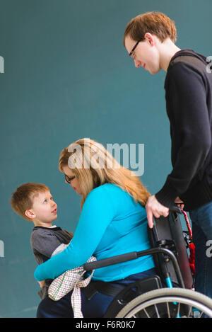 Man pushing paraplegic wife and son - Stock Photo