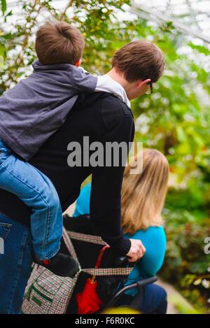 Man pushing paraplegic wife and carrying son piggyback - Stock Photo