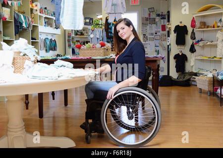 Pregnant paraplegic woman in wheelchair shopping in baby store - Stock Photo