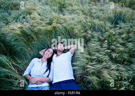 Couple laying in grass - Stock Photo
