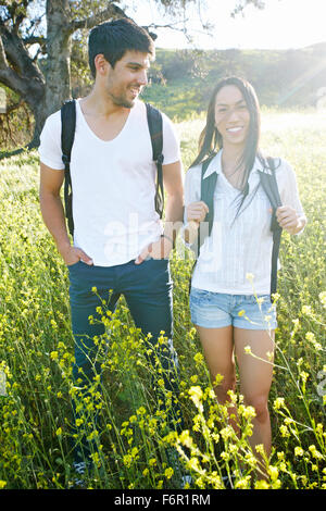 Couple carrying backpacks in field - Stock Photo