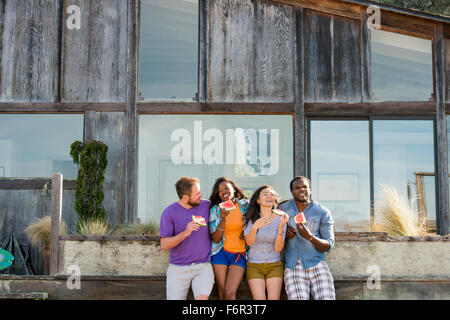Friends eating watermelon in backyard - Stock Photo