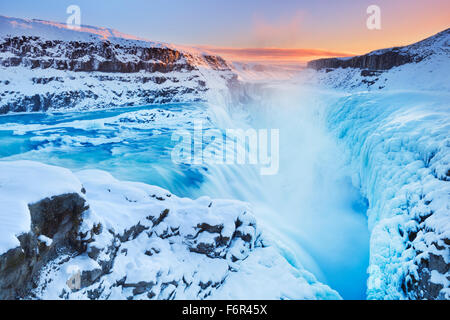 The Gullfoss Falls in Iceland in winter when the falls are partially frozen. Photographed at sunset. - Stock Photo