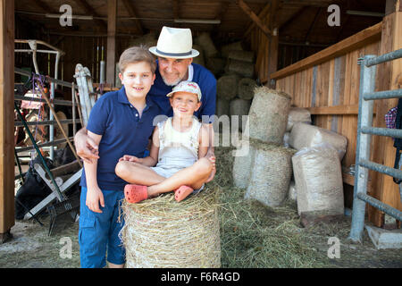Grandfather and grandchildren in stable - Stock Photo