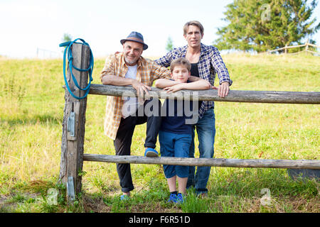 Portrait of multi-generation family by fence - Stock Photo