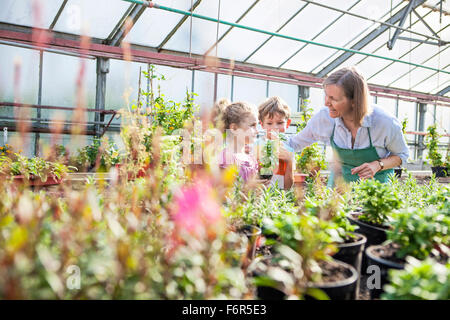 Female gardener and children in greenhouse - Stock Photo